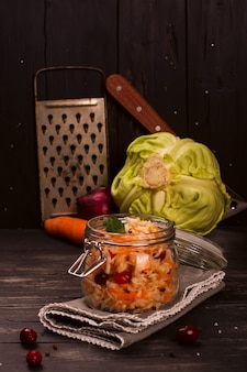 Sour cabbage in a glass jar over wooden background, rustic style