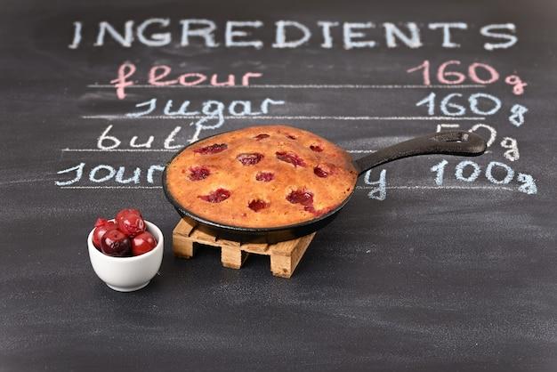 木製のトリベットの鍋にサワーチェリーケーキ背景にチョークで書かれた材料