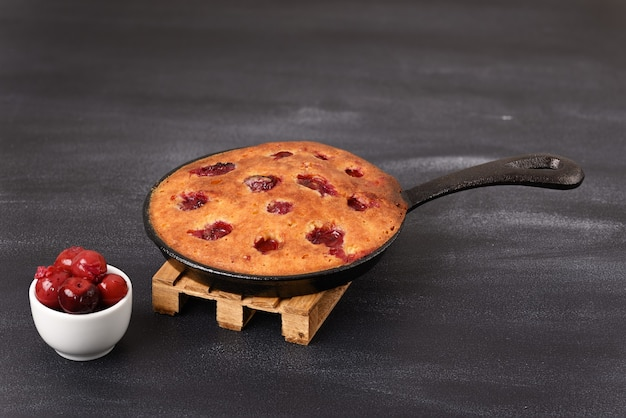 Sour cherry cake in a pan on a wooden trivet