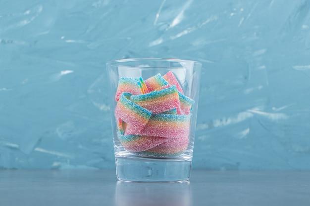 Кислые жевательные конфеты в стекле на каменном столе.