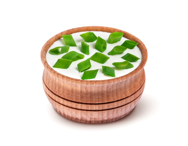 Sour cream and green onion in wooden bowl isolated on white