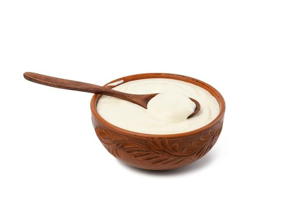 白い背景に分離された木のスプーンと茶色のセラミックボウルのサワークリーム、発酵乳有用な製品