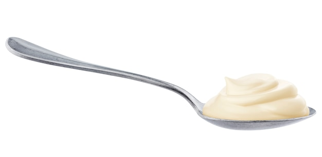 Sour cream in spoon isolated on white