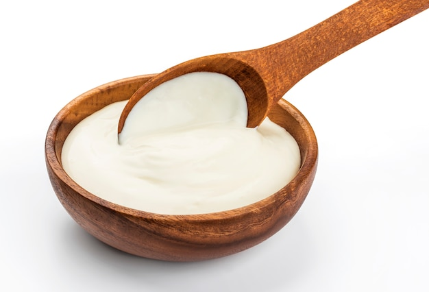 Sour cream in wooden spoon isolated on white