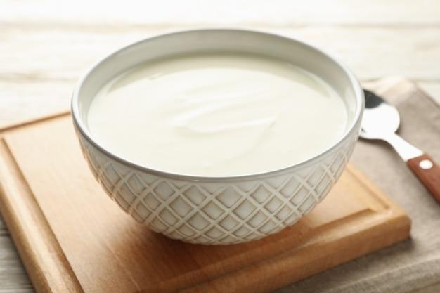 Сметанный йогурт, ложки и салфетка на белом деревянном