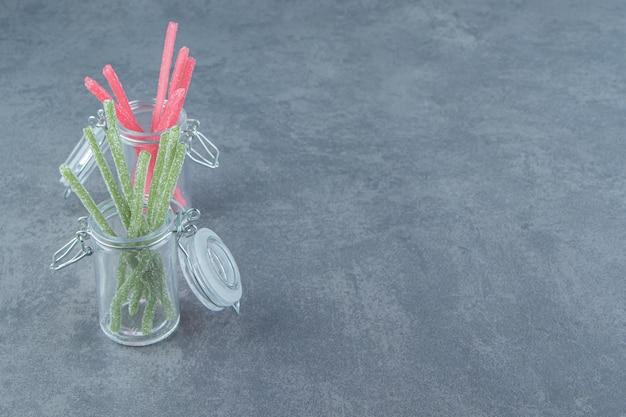 Caramelle di gelatina acida in contenitori di vetro.