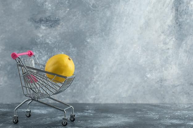 Limone acido posto in un piccolo carrello della spesa