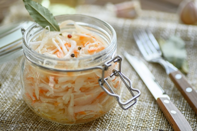 Sour, pickled sauerkraut with carrots and bay leaves in a glass jar.