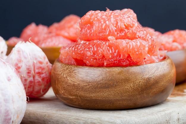 Кислый спелый грейпфрут, очищенный и разделенный на дольки, розовый грейпфрут, готовый к употреблению, крупный план