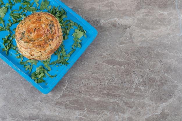 大理石の表面の青い大皿に酸っぱいショアゴーガルとパセリの葉
