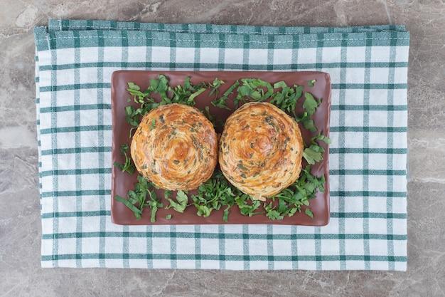みじん切りのパセリの葉で飾られた大皿、タオル、大理石の表面に酸っぱいショアショアゴーガル