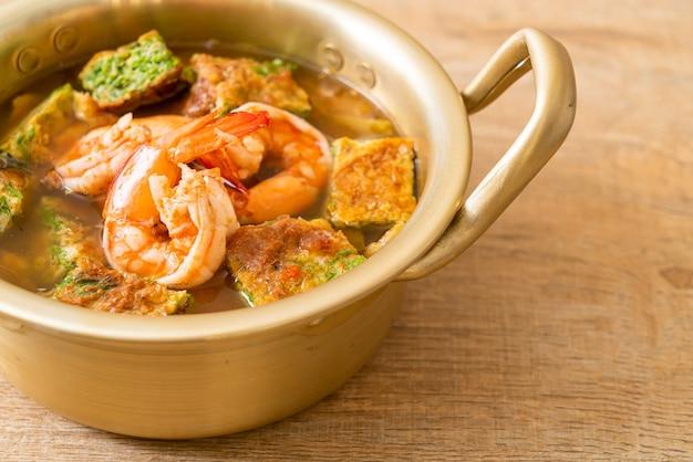 エビと野菜のオムレツを添えたタマリンドペーストの酸味のあるスープ - アジア料理スタイル
