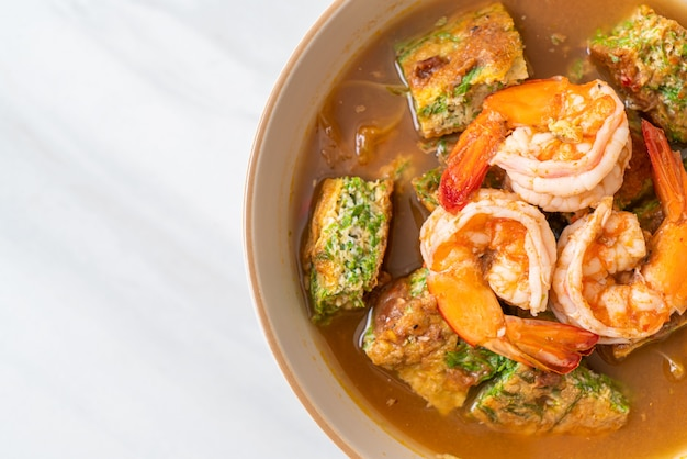 Sour soup made of tamarind paste with shrimps and vegetable omelet - asian food style