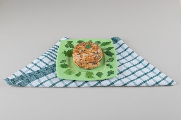대리석 배경에 접힌 수건에 파슬리 잎으로 장식 된 플래터에 신 과자.