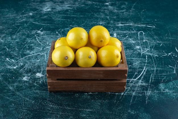 Кислые желтые лимоны в деревянной коробке.