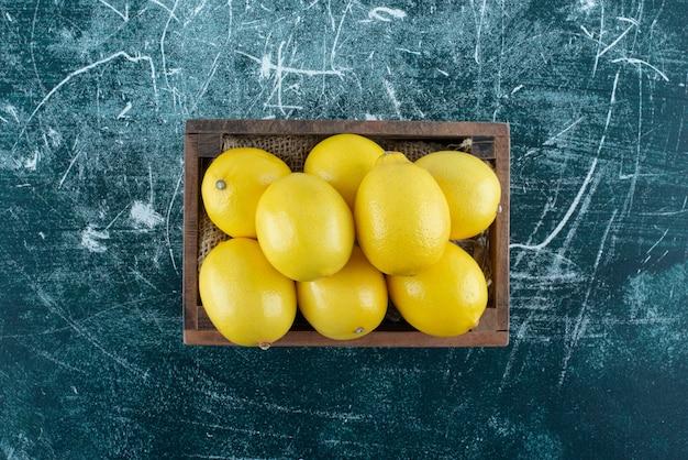 木製の箱に黄色いレモンを酸っぱくします。