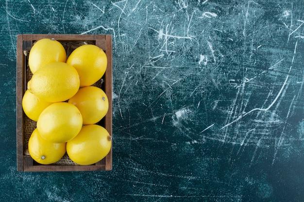 나무 상자에 신 노란색 레몬.
