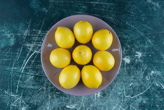 紫の皿に黄色いレモンを酸っぱくします。