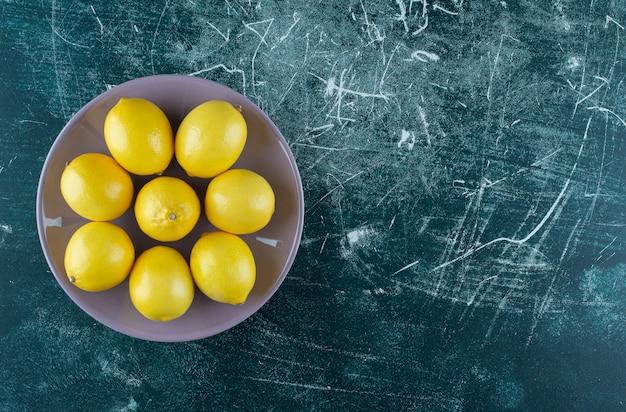 보라색 접시에 신 노란색 레몬.