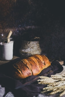 A sourdough bread  with wheat spikes aside