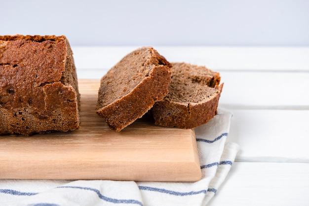 사워도우 호밀 빵은 복사 공간이 있는 흰색 나무 테이블에 있는 커팅 보드에 얇게 썬 것입니다.