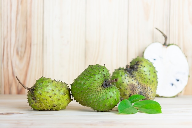 Soursop fruit on wooden table.