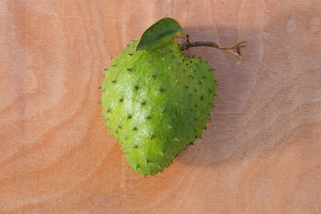 Soursop, prickly custard apple on wooden table.