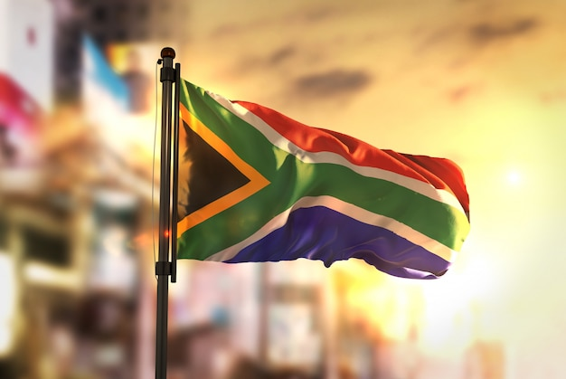South africa flag against city blurred background at sunrise backlight