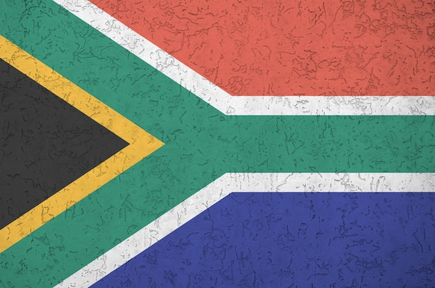 South africa flag depicted in bright paint colors on old relief plastering wall. textured banner on rough background