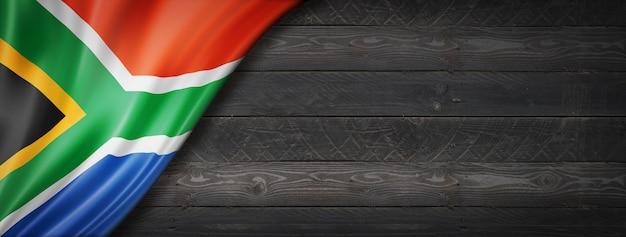 黒い木の壁に南アフリカの旗。水平方向のパノラマバナー。