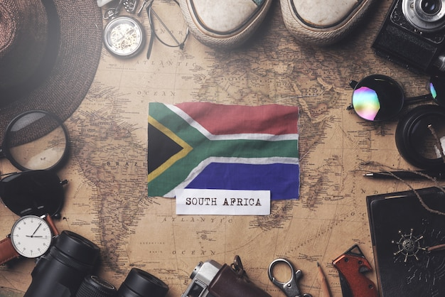 South africa flag between traveler's accessories on old vintage map. overhead shot