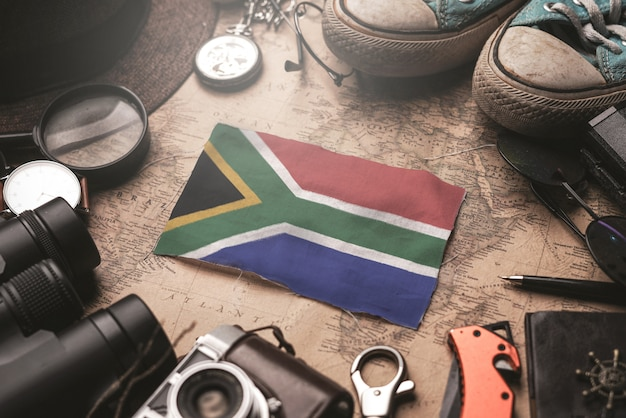 South africa flag between traveler's accessories on old vintage map. tourist destination concept.