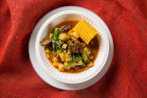Южноамериканская кухня: суп puchero с крупным планом нута в горшочке на столе.