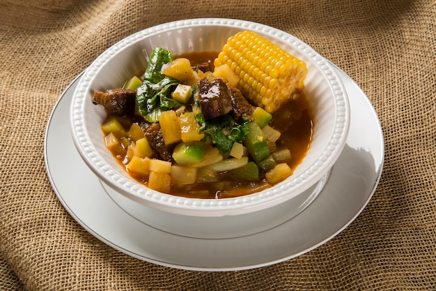 South american cuisine: puchero soup with chickpeas close-up in a pot on the table.