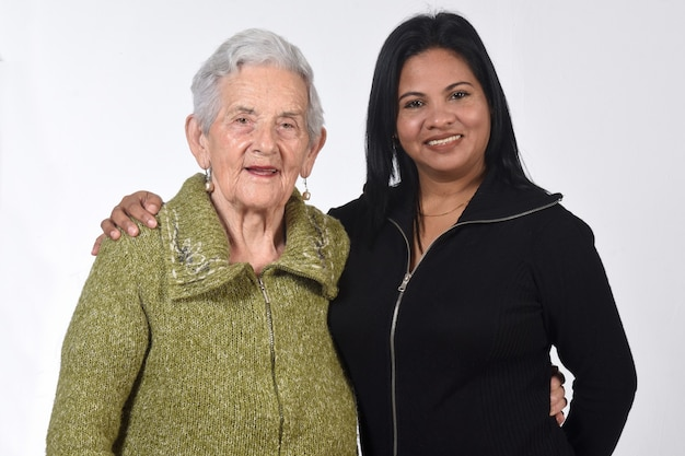 South american girl caring for an old woman over white wall
