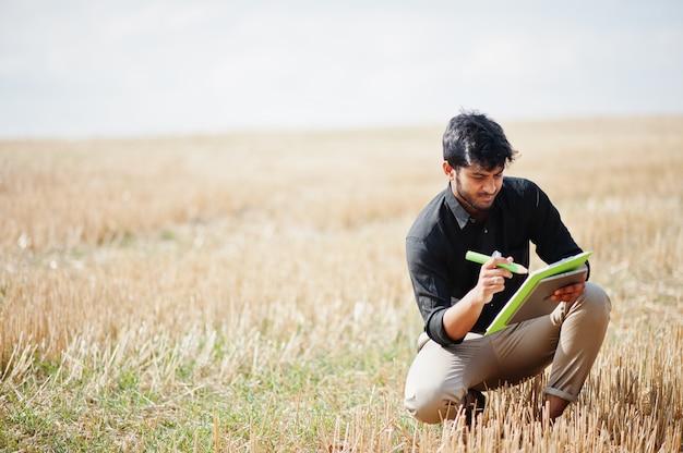 Южный азиатский фермер агронома проверяя ферму пшеничного поля. концепция сельскохозяйственного производства.