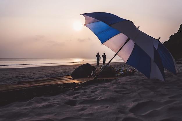 サウスビーチマイアミビーチの傘とラウンジチェア。海に沈む美しい夕日を背景に、人けのない人けのないビーチに横たわる白と青の2つの傘。