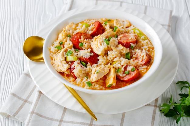 Тушеное мясо с курицей и рисом из южной каролины под названием куриное болото с копченой колбасой, луком-пореем, приготовленное в курином бульоне, подается на белой тарелке