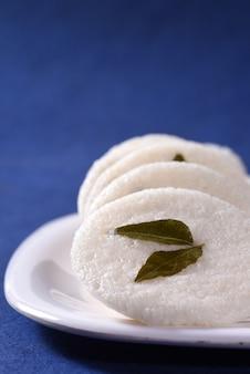 南インド料理のベジタリアン朝食イドゥリまたはお皿の中でぼんやりと。