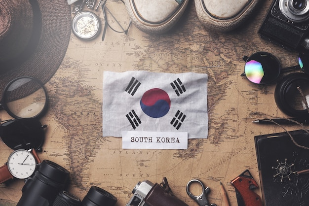 South korea flag between traveler's accessories on old vintage map. overhead shot