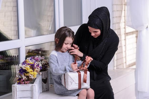 Девушка юго-восточной азии с подарочной коробкой. образ жизни мусульманской семьи. счастливые улыбающиеся малайские родители и ребенок.