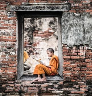Southeast asian novice monk reading book outside monastery, buddhist teaching.