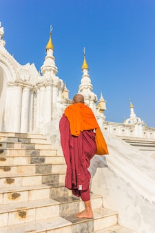 Southeast asian young buddhist monks walking morning alms in inle, myanmar
