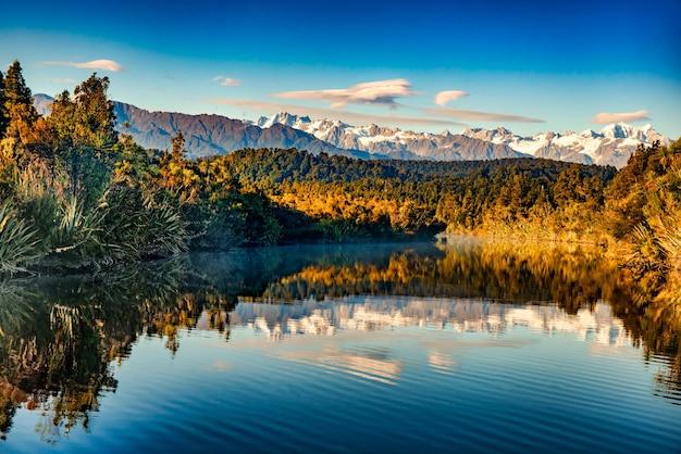 Южные альпы отражаются в лагуне окарито на западном побережье новой зеландии на рассвете