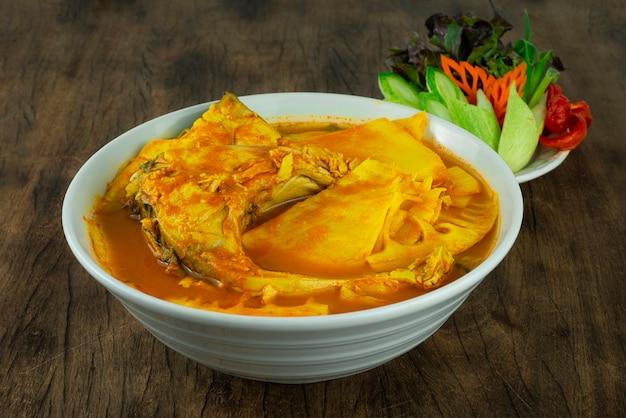 Южный кислый суп с рыбой и консервированными побегами бамбука желтый карри кислый и пряный тайский кулинарный стиль подается с резными овощами, вид сбоку