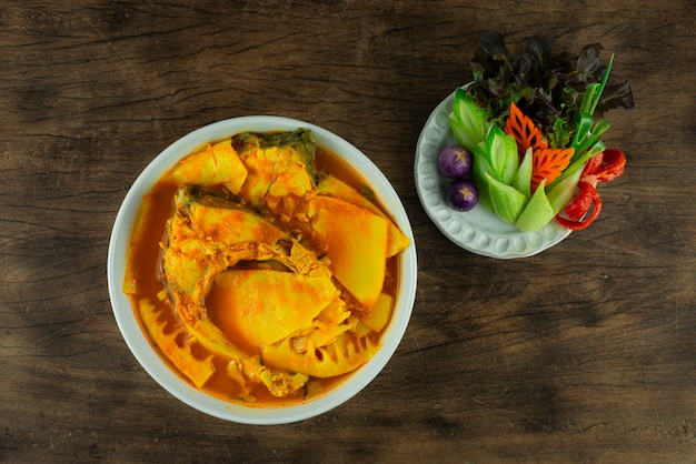 Южный кислый суп с рыбой и консервированными побегами бамбука желтый карри кислый и пряный тайский кулинарный стиль подается из резных овощей topview