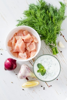 Souvlaki and ingredients, white wood background