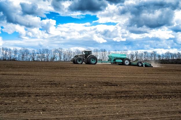 春の畑での播種作業。シーダー付きトラクター。