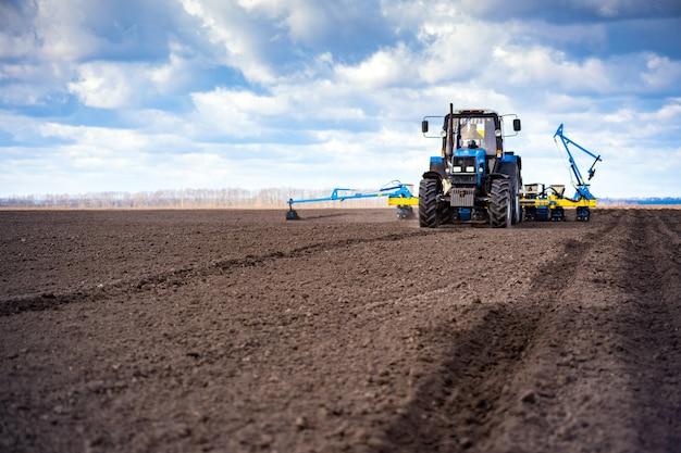 Посевные работы в поле весной. трактор с сеялкой.