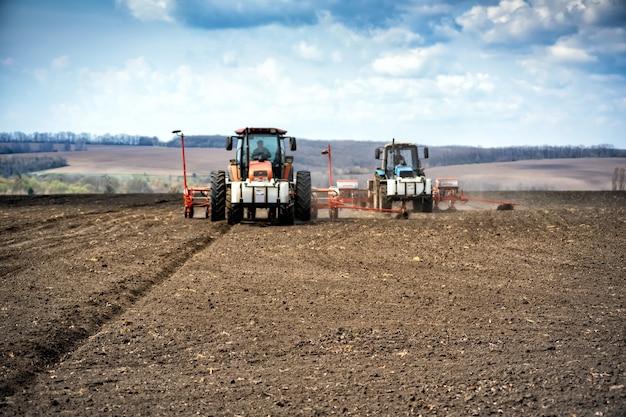 Посевные работы в поле. трактор с сеялкой.
